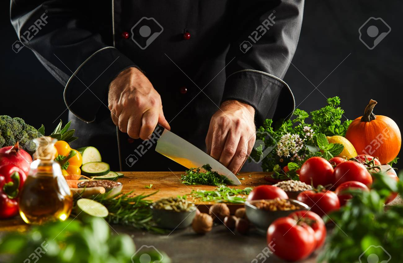 Chef dicing fresh herbs on a wooden chopping board with a kitchen knife while preparing salad in a close up on the hands - 115257958