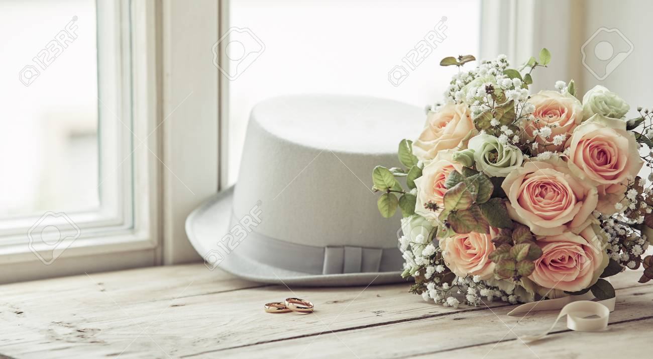 Marriage day composition of groom's white hat, wedding rings and bridal bouquet of pink roses, sitting on wooden window sill - 116545879