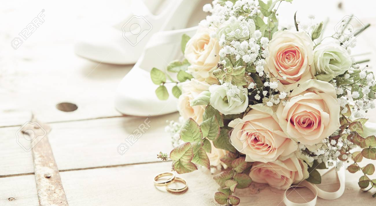 Marriage day composition with shoes, pink roses flowers bridal bouquet and wedding rings viewed from high angle on wooden background - 116539342