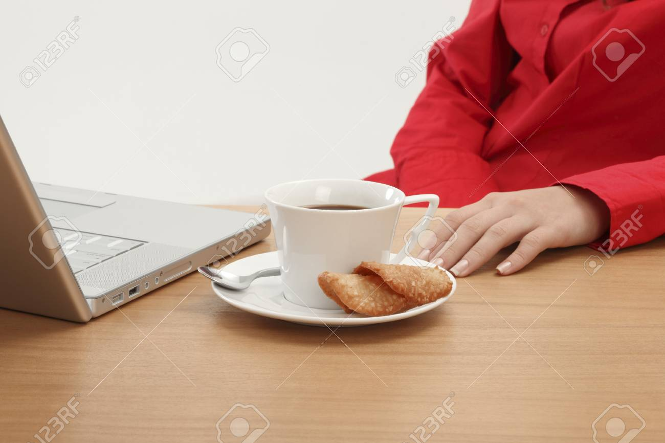Having a cup of coffee sitting at a desk by the computer Stock Photo - 17027152