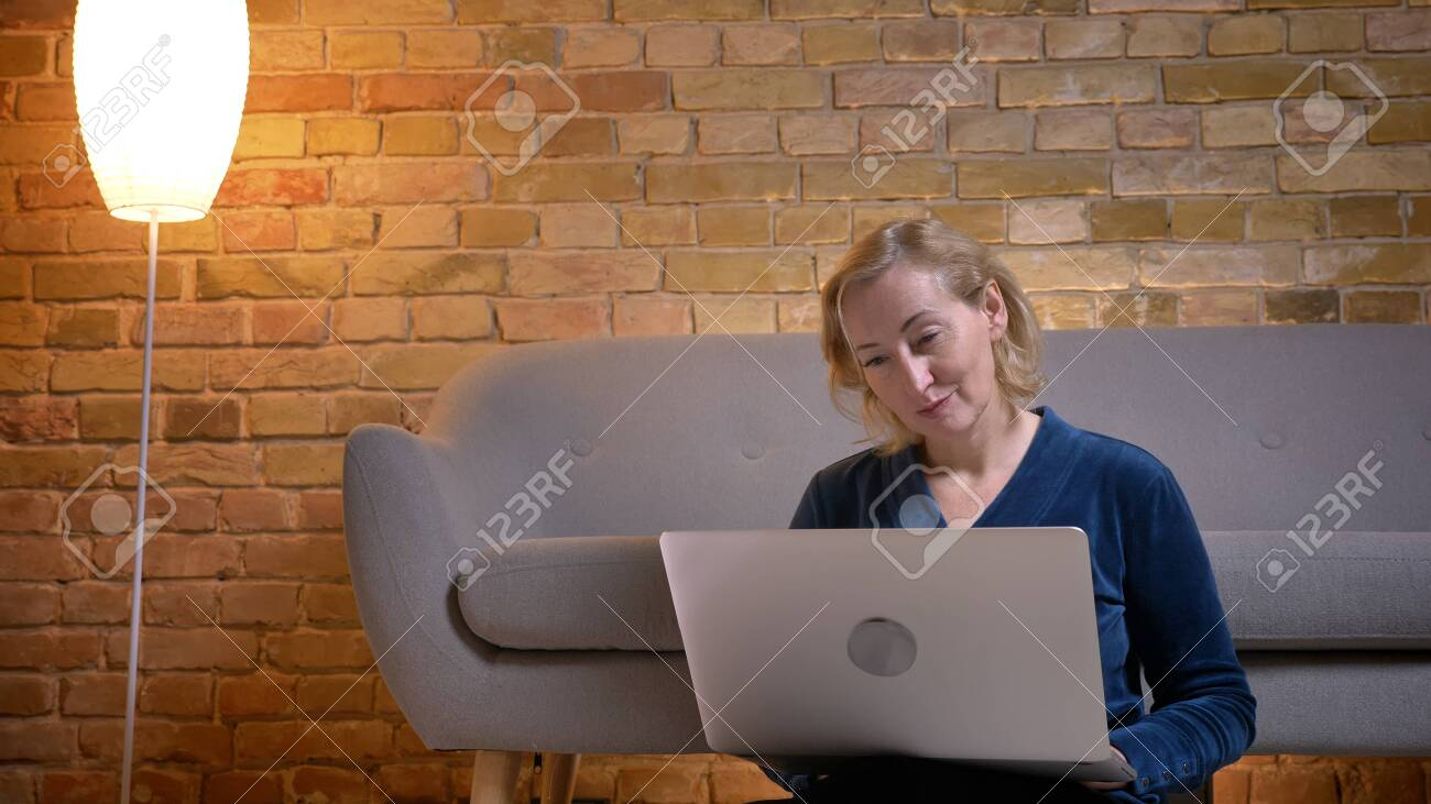 Portrait of senior caucasian lady sitting on floor and working with laptop with positive surprise in cozy home atmosphere. - 120071887