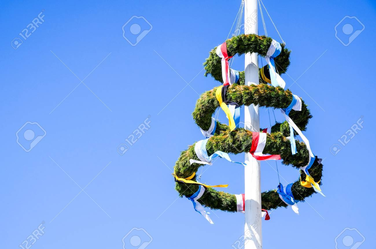typical bavarian maypole in front of blue sky - 73252832