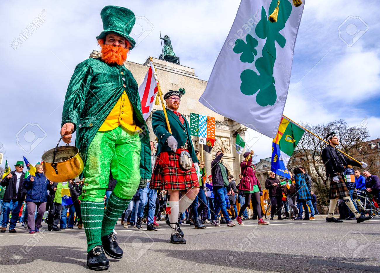 MUNICH - MARCH 11: People celebrating the annual national irish holiday St. Patricks day marching in the old town in munich, germany on March 11, 2018 - 107957900