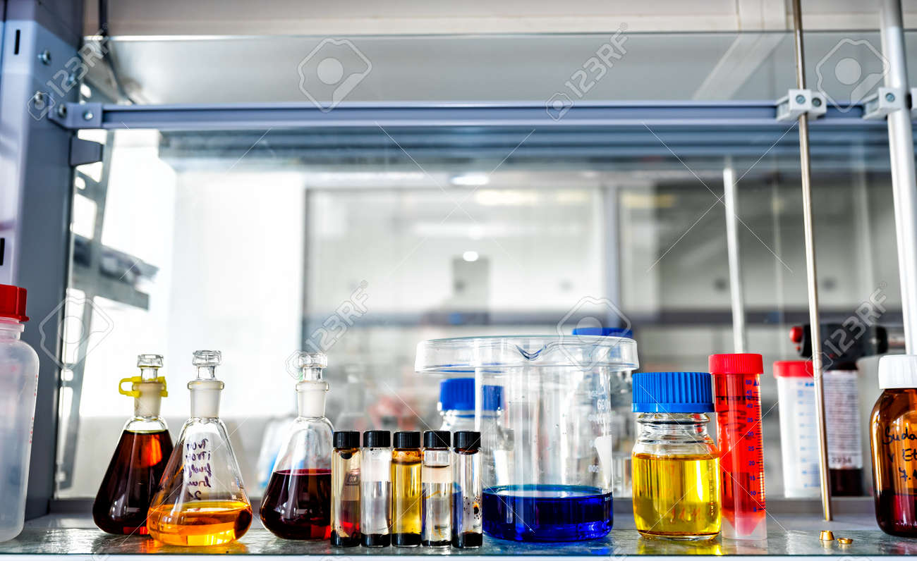Closeup of laboratory glassware filled with various colored liquids, science and research background, selective focus - 164385426