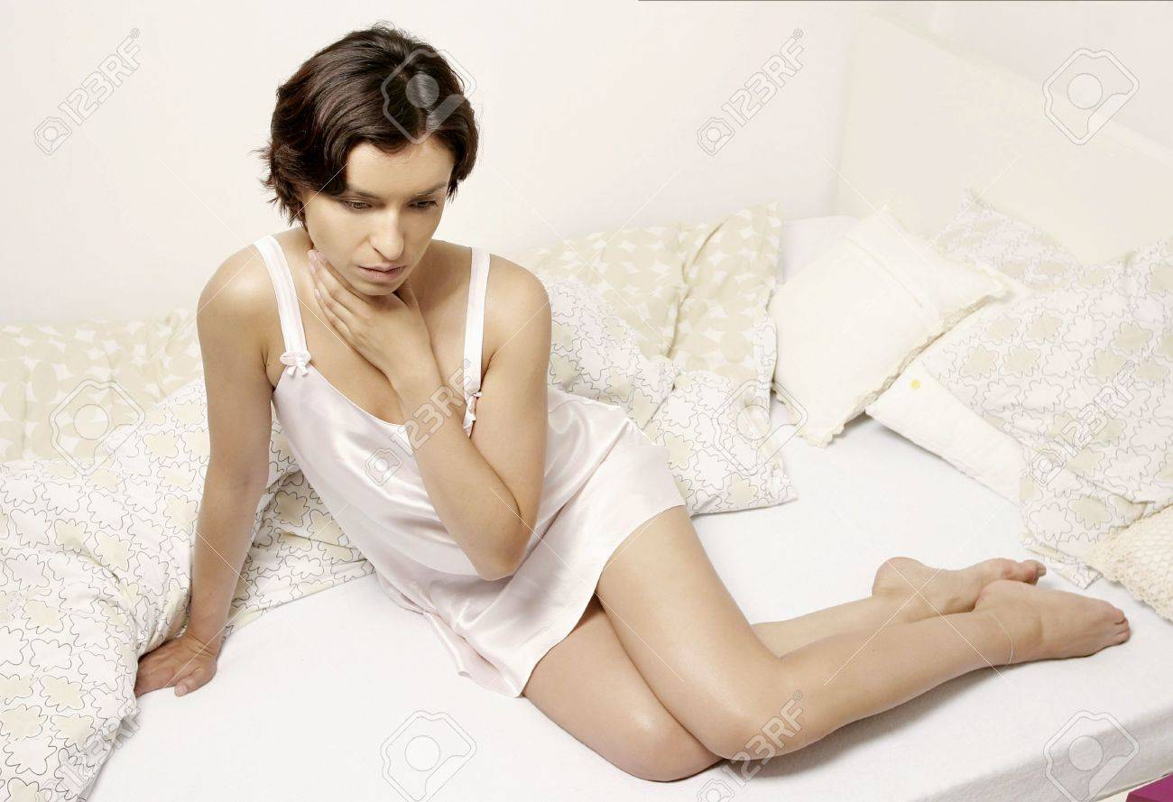 young woman girl in a white nigh dress lying in bed stock photo