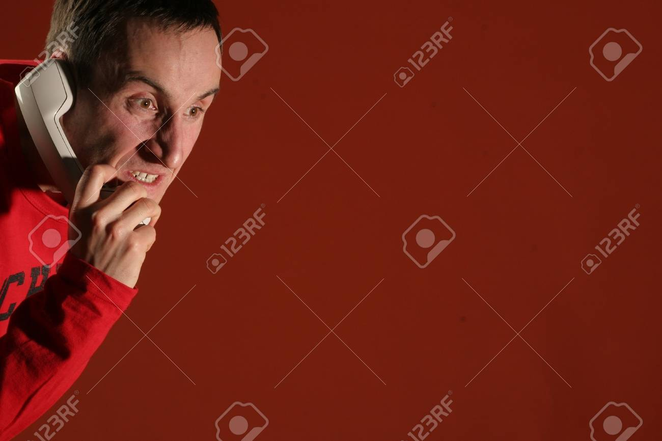 Young man in a red pullover screaming on the phone - isolated  background. Stock Photo - 2180030