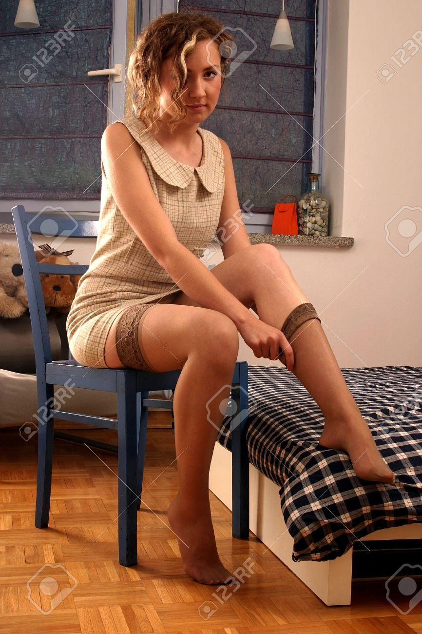Young blonde beautiful girl sitting on a chair and putting on stocking. Stock Photo - 2180069