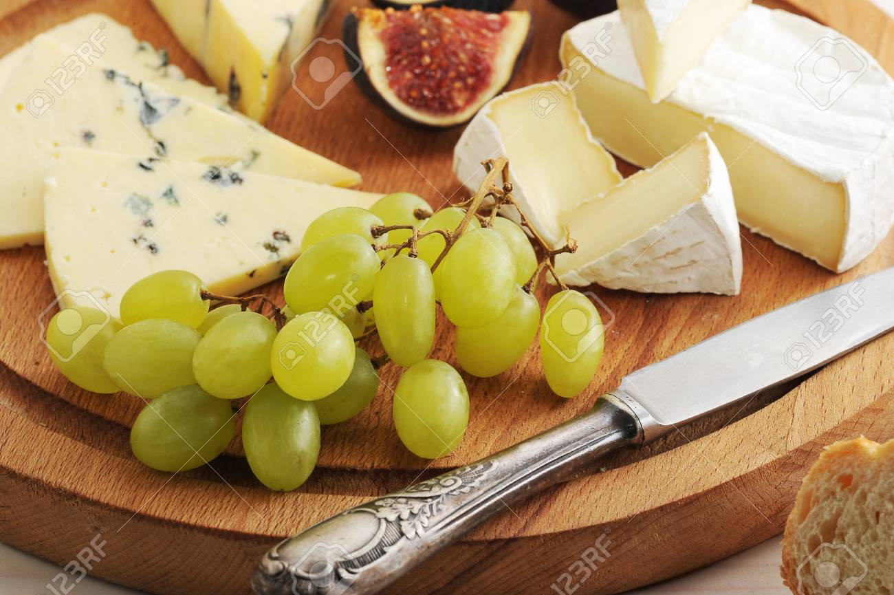 cheese plate - various types of cheeses and figs and grapes on a white wooden background & Cheese Plate - Various Types Of Cheeses And Figs And Grapes On ...