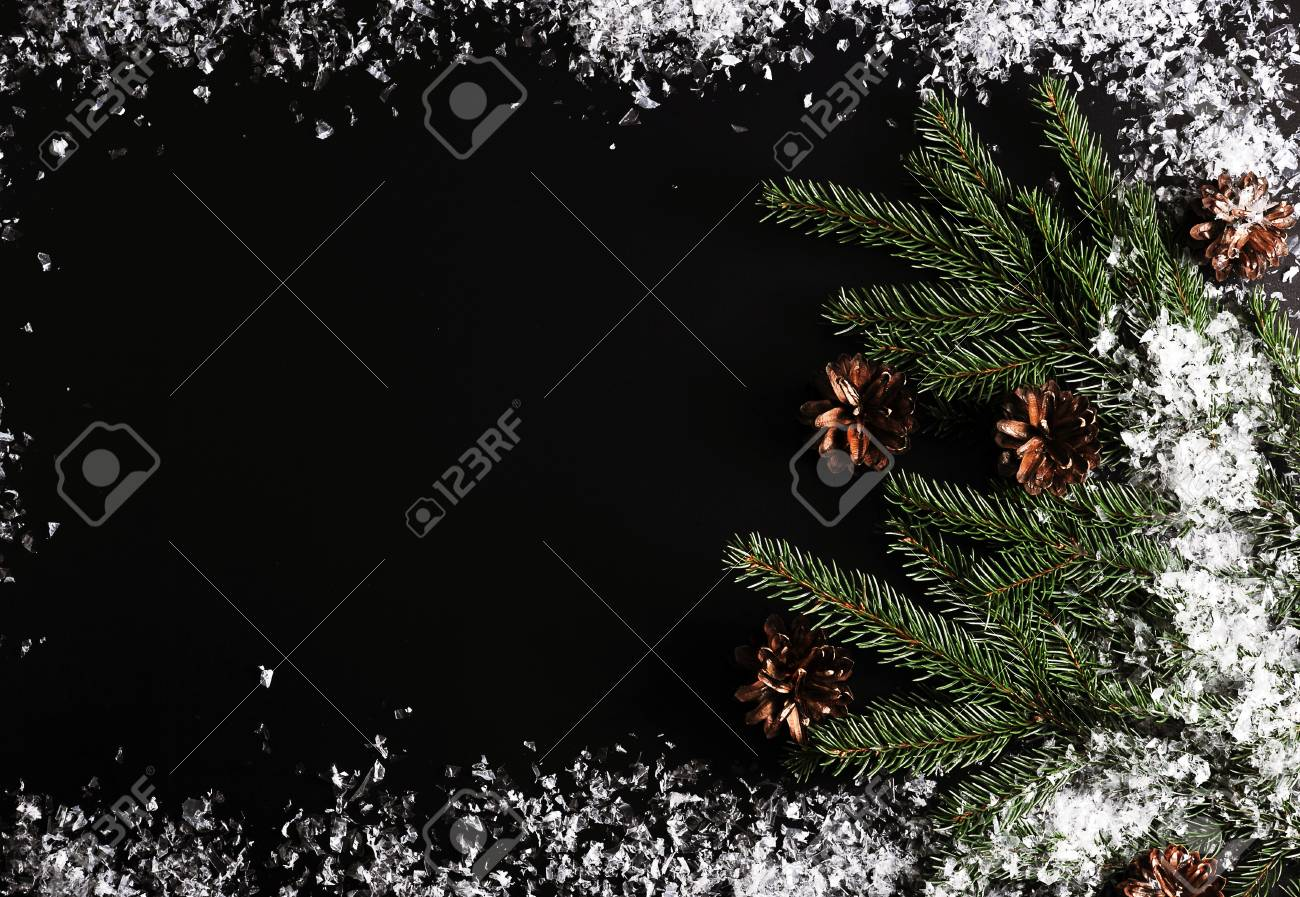 background for new year greetings tree branches cones and snow on a black background