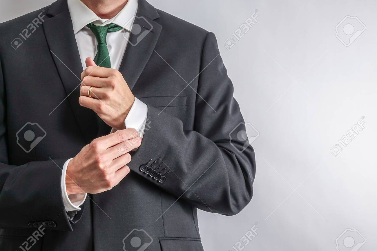 Well Dressed Businessman In White Shirt And Black Suit Adjusting