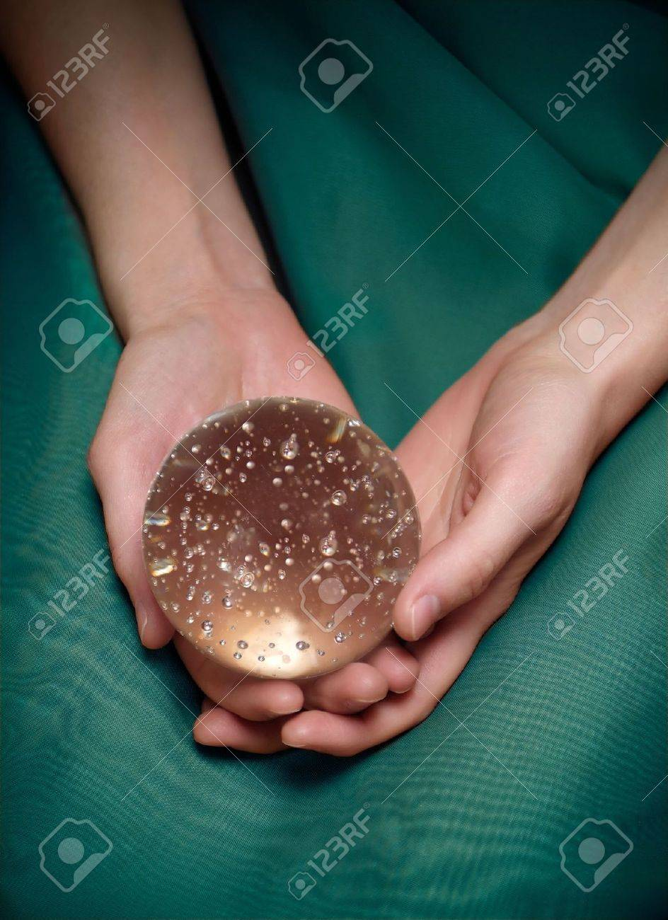 Woman's hands holding a crystal ball. Closeup, sparkly bubbles in the ball Stock Photo - 2408346
