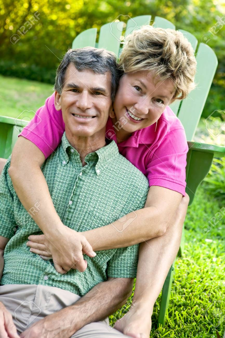 Attractive mature man and woman hugging and happy in their backyard Stock Photo - 5259367