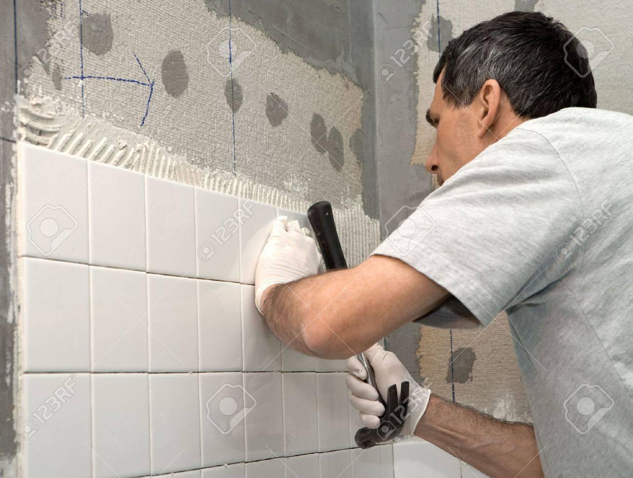 Uomo di impostazione delle mattonelle a bordo di cemento egli è