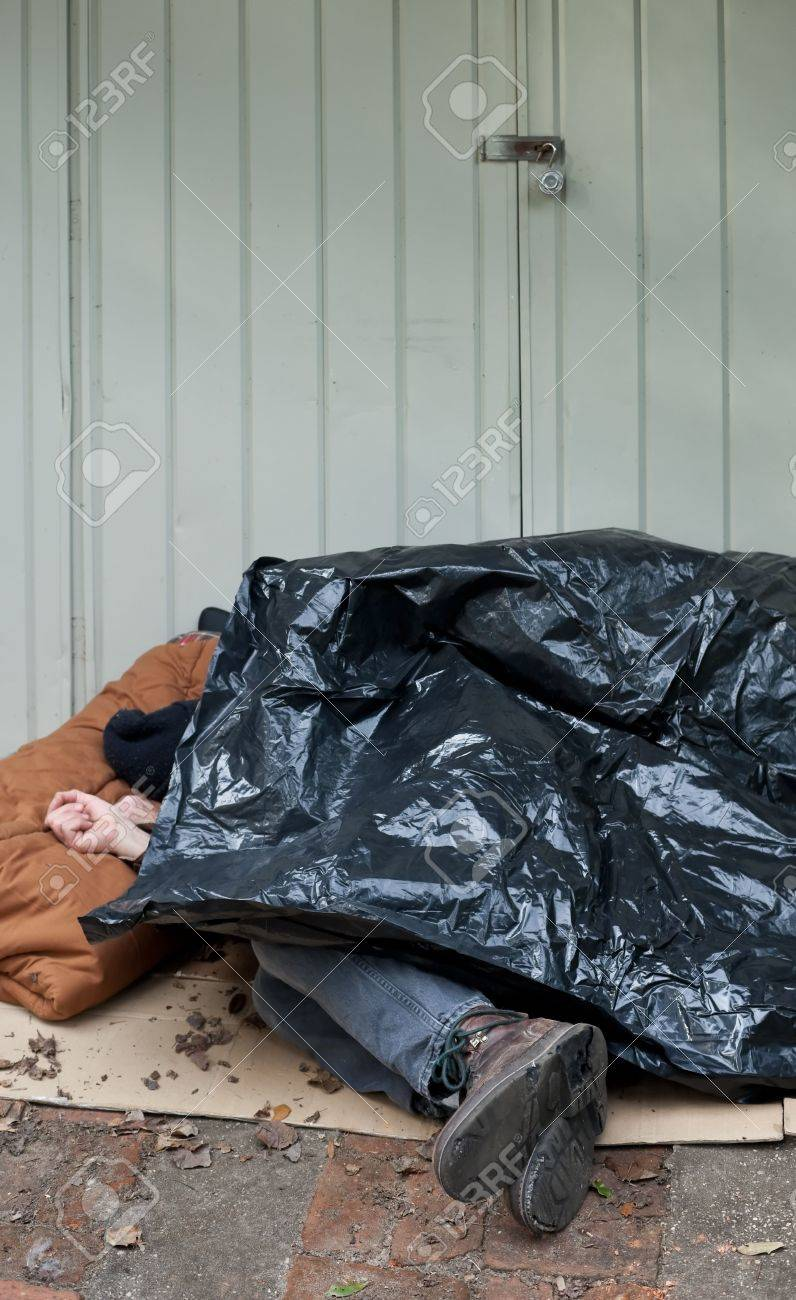 homeless man curled up asleep under a plastic tarp on the street stock photo