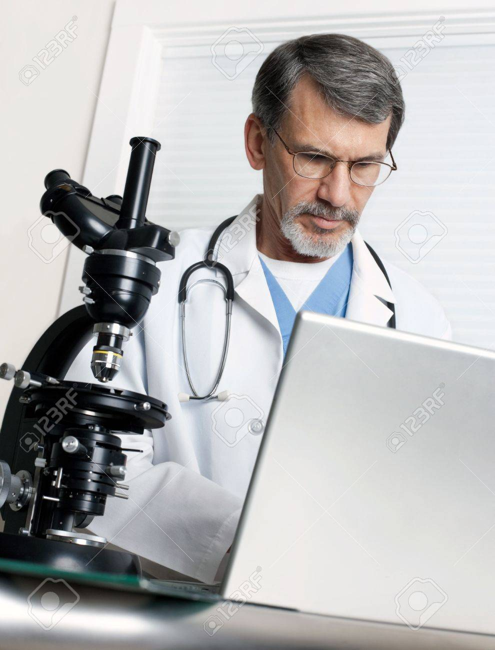 a doctor researching at the microscope and laptop computer stock a doctor researching at the microscope and laptop computer stock photo 6442856