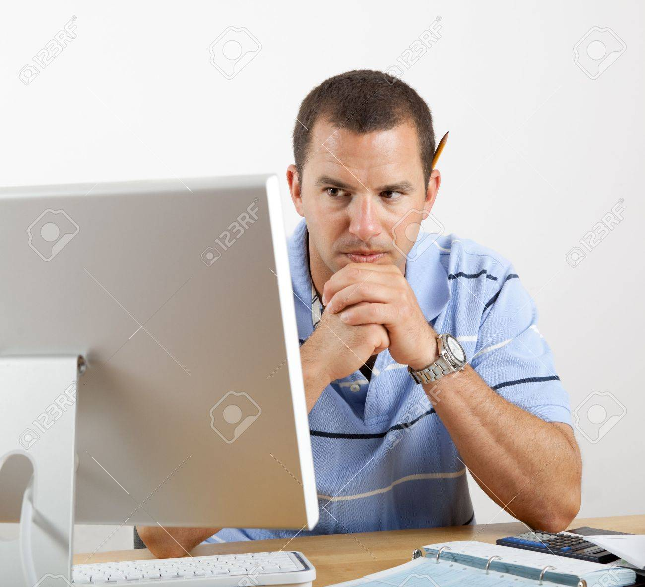 Young man at desk with computer, checkbook and calculator, worrying about paying the bills. Stock Photo - 7036614