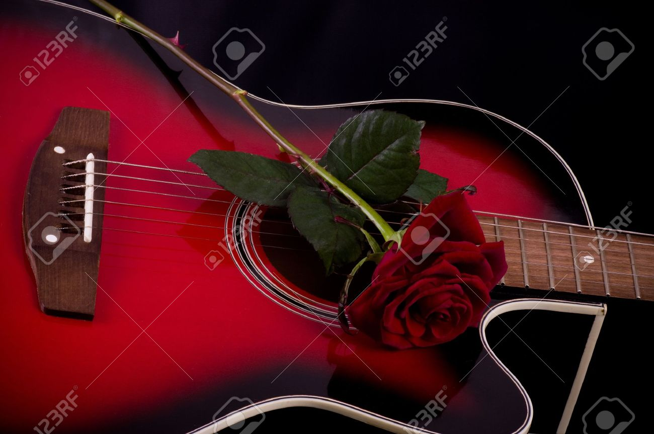 Beautiful Red Guitar With Rose On Black Background Stock Photo