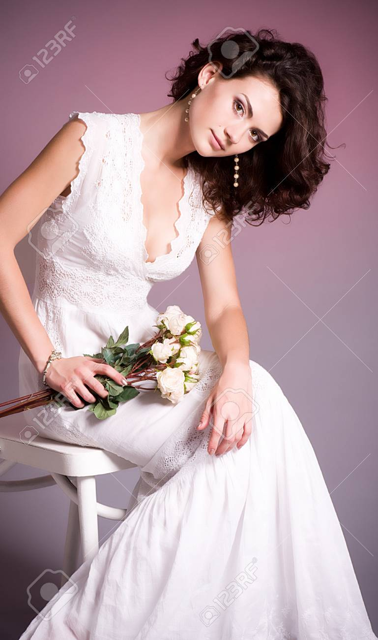 Young woman in retro bridal dress with bouquet from roses  on background Stock Photo - 13816924