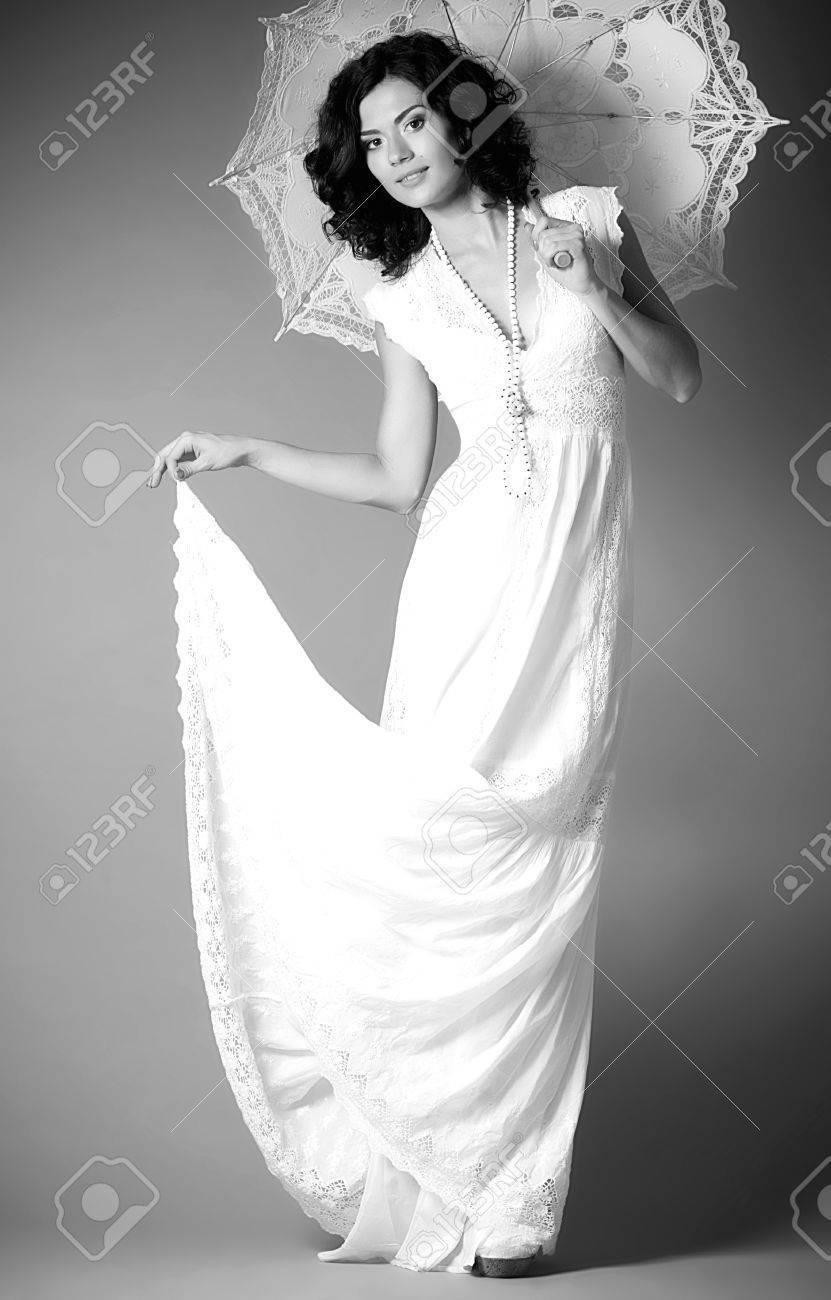 0cbf5bc0ce7f Archivio Fotografico - Giovane donna in abito da sposa retrò con ombrello