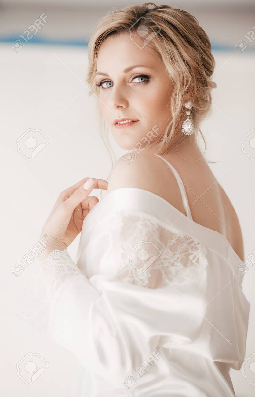 Beautiful blonde bride with stylish make-up in white dress - 130994538
