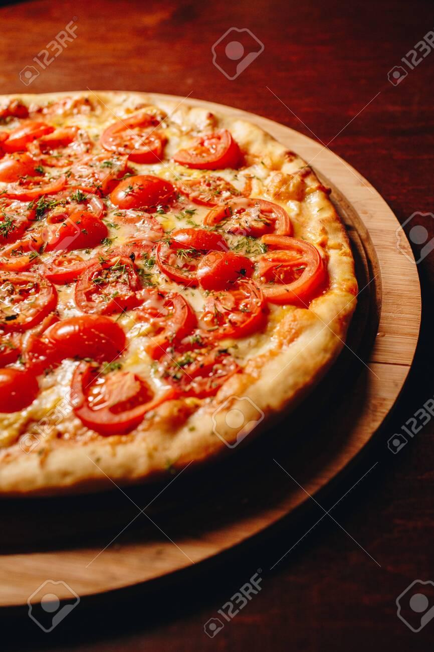 Stock Photo - Fresh delicious Italian pizza on a dark background - 145778827