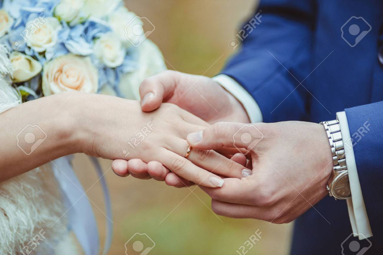 Grooms hand putting a wedding ring on the brides finger stock grooms hand putting a wedding ring on the brides finger stock photo 25274100 junglespirit Images