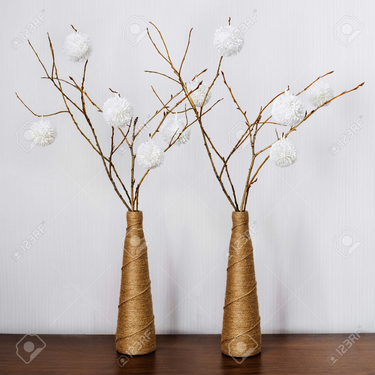 Vase With Dry Branches Adorned With White Balls On A Wooden Table ...