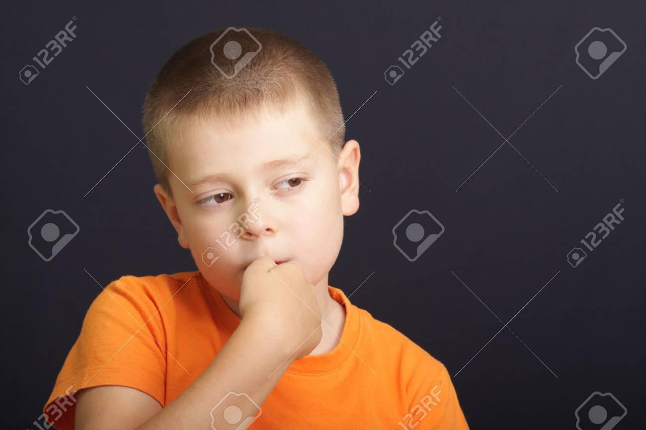 Boy in orange shirt nerviously bites nails over dark background Stock Photo - 3524526
