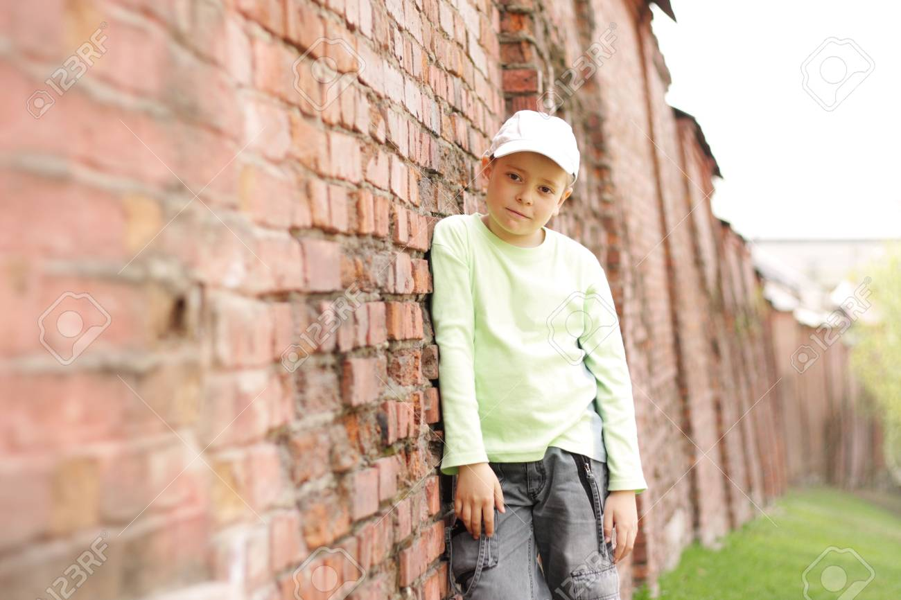 Boy in casual standing at old long red brick wall Stock Photo - 4807496