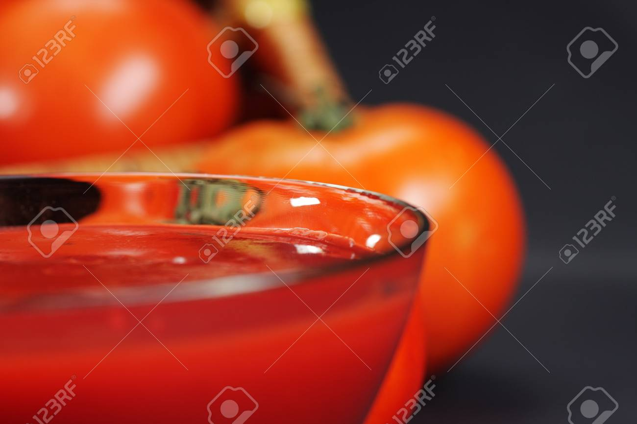 Ketchup in bowl with tomatoes on back closeup photo selective focus Stock Photo - 6049162