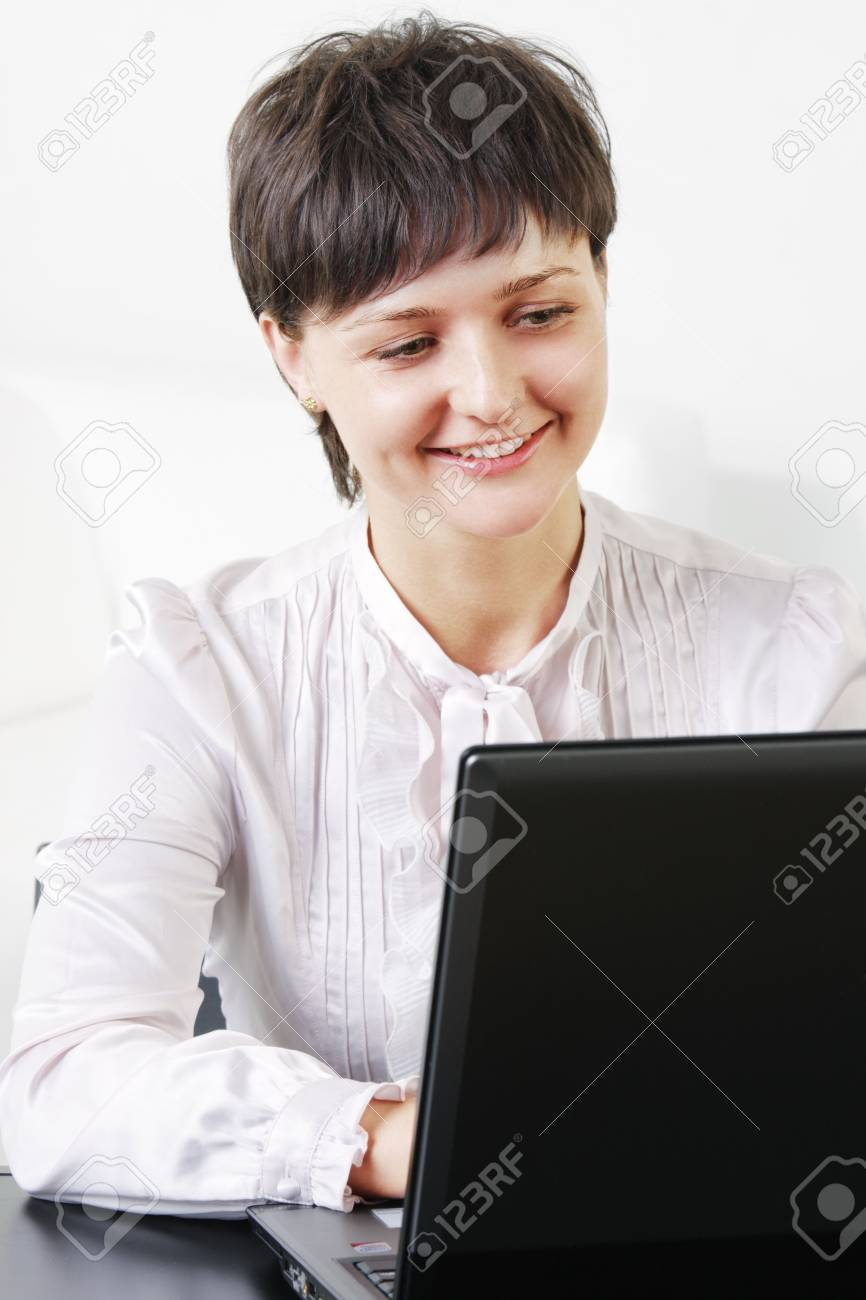 Smiling young brunette businesswoman working on laptop Stock Photo - 6286423