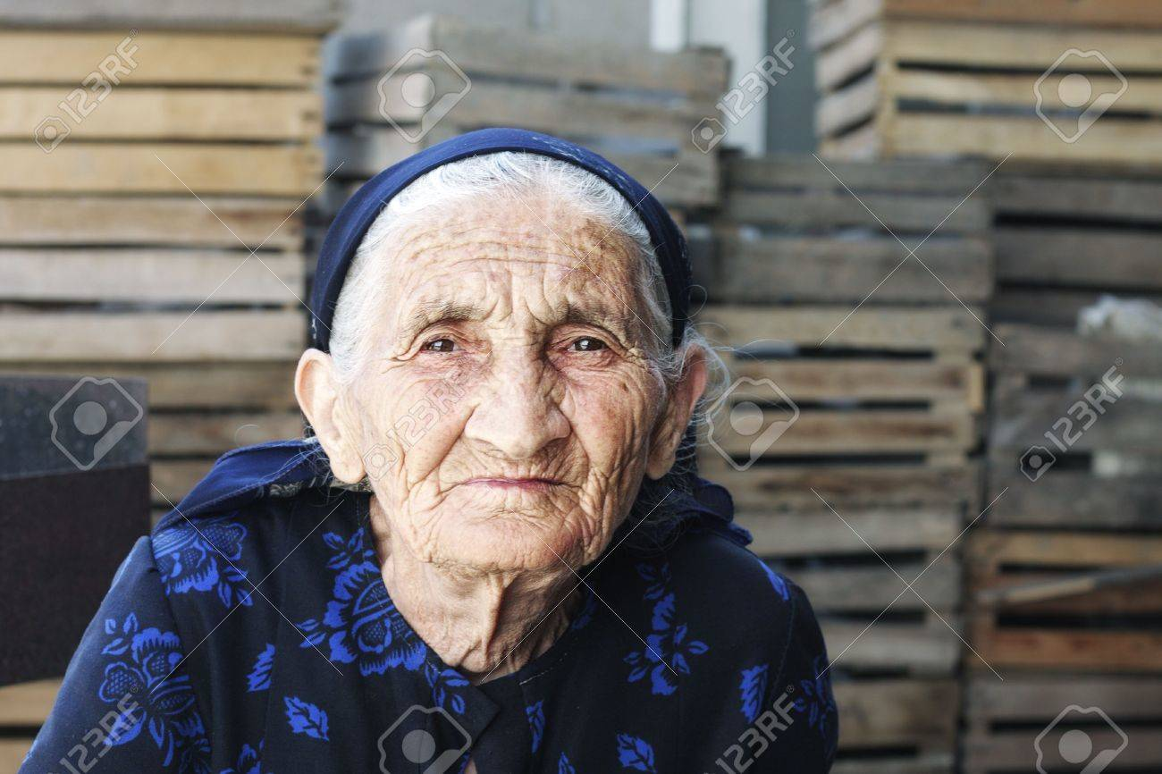 Elderly woman in black dress sitting outdoor with wooden cases on background Stock Photo - 6376678
