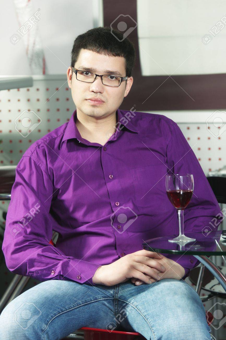 Serene Guy Wearing Purple Shirt Sitting In Cafe With Glass Of ...
