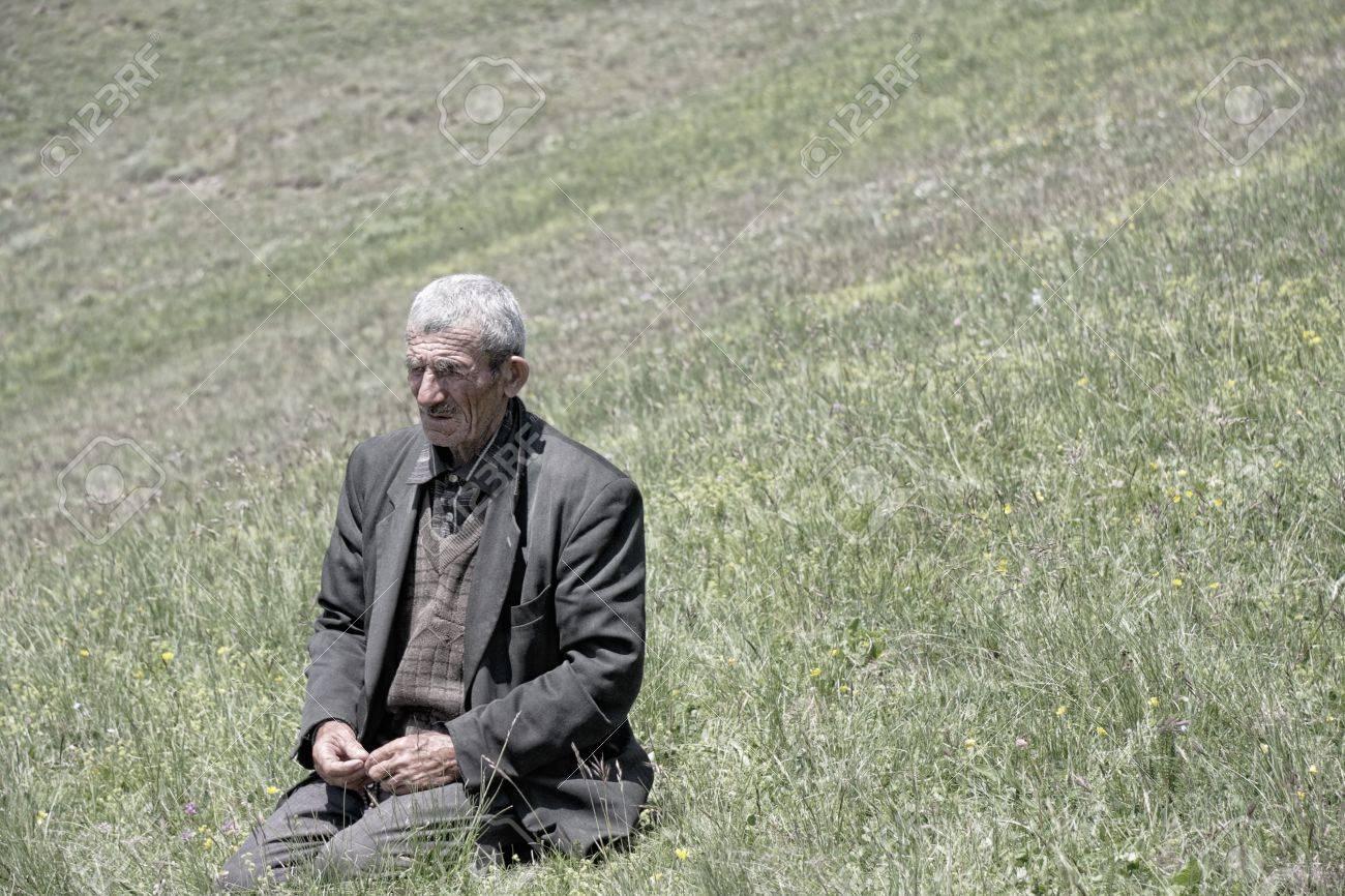 Senior man sitting on his knees in meadow Stock Photo - 11307807