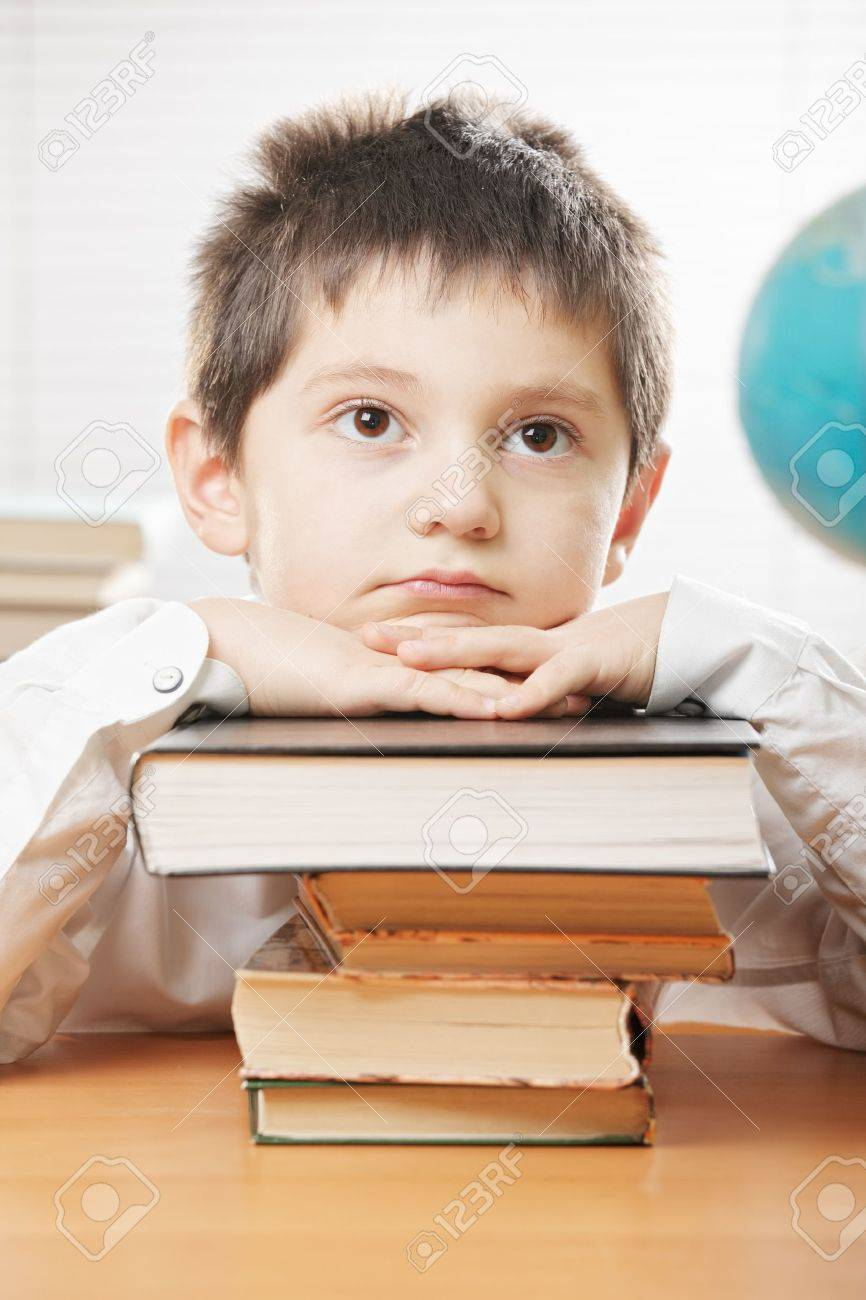Boring boy sitting at desk and leaning on stack of books Stock Photo - 15042600