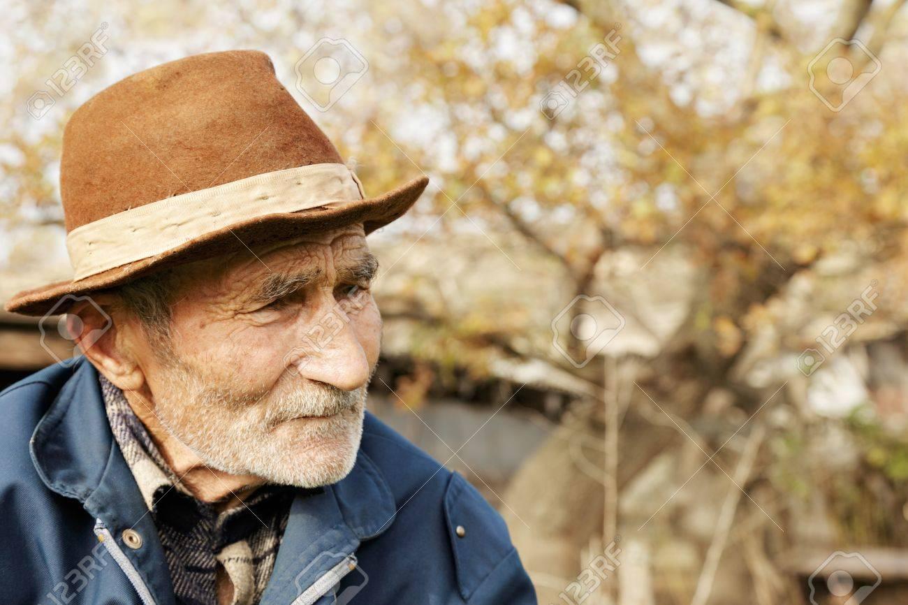 Sad senior man in hat looking sideways outdoor portrait Stock Photo - 15867322