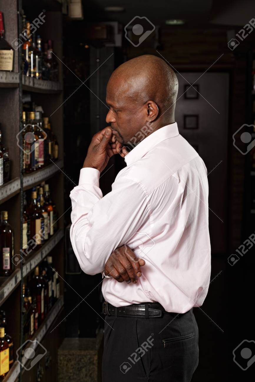 African guy in a wine shop examining shelves Stock Photo - 16142258