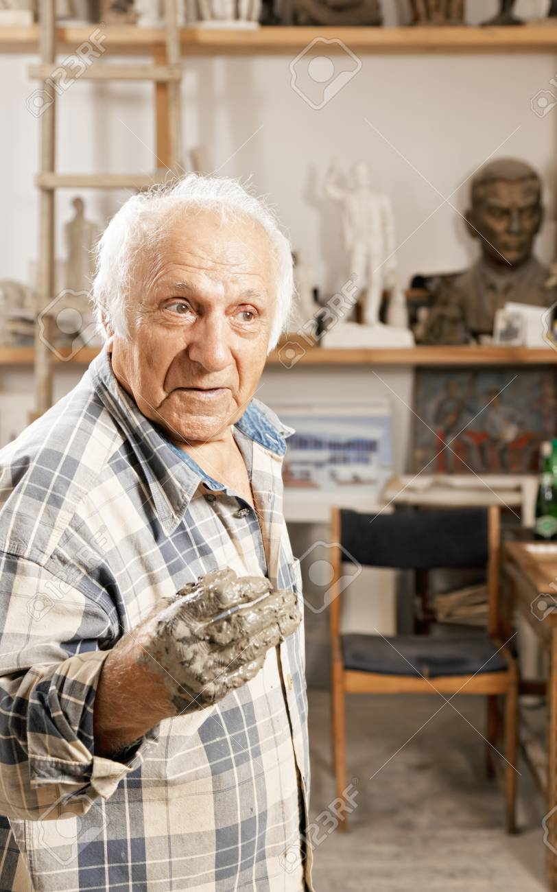 Senior sculptor with hands soiled with clay talking and looking sideways Stock Photo - 16469202