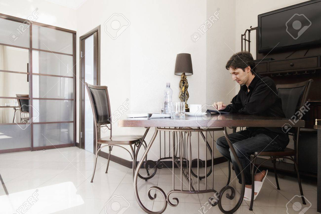 Guy working on tablet computer while sitting at the table Stock Photo - 21889709