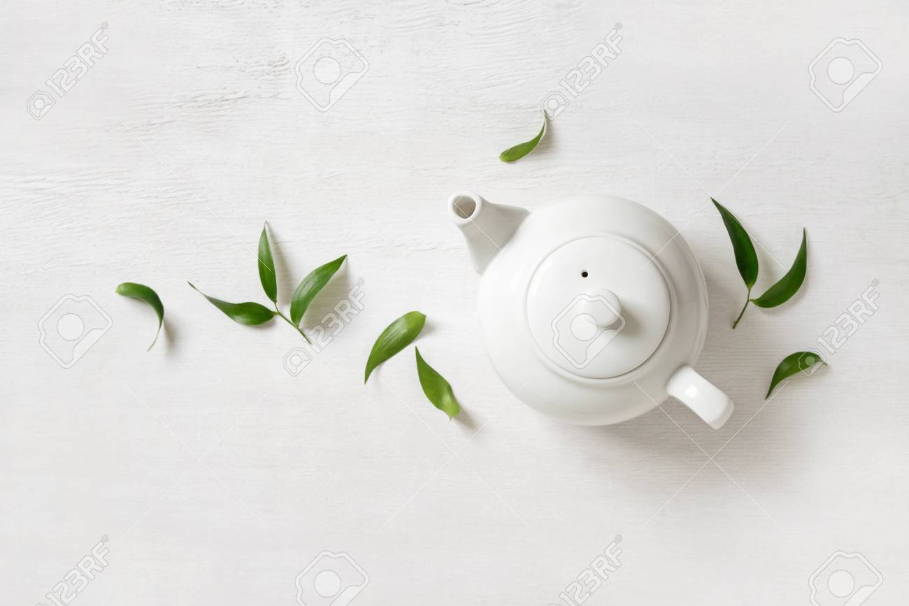 Tea Concept Teapot With Tea Surrounded With Green Tea Leaves Stock Photo Picture And Royalty Free Image Image 73370377