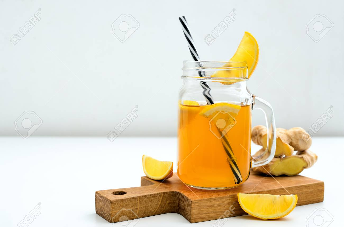 Ginger and lemon combucha detox drink in a jar with a straw,
