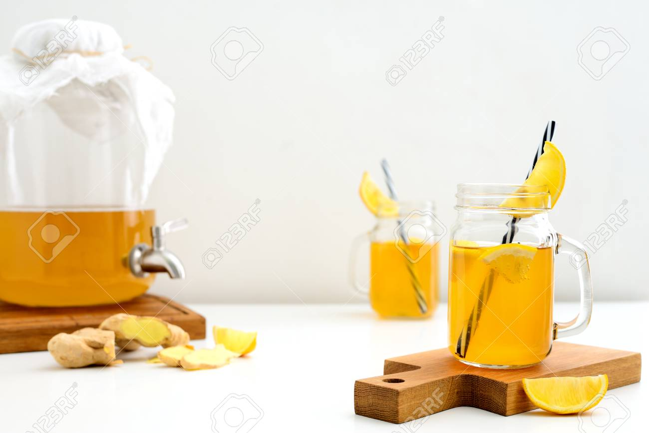 Ginger and lemon combucha detox drink in two jars with straws,