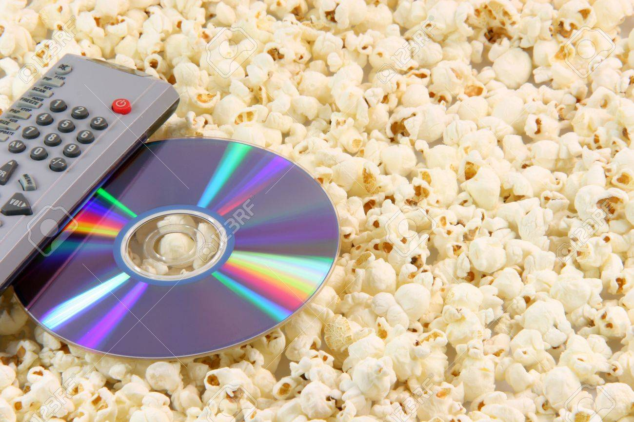 television remote control and dvd disc movie on pop corn background food and entertainment conceps - 2303118