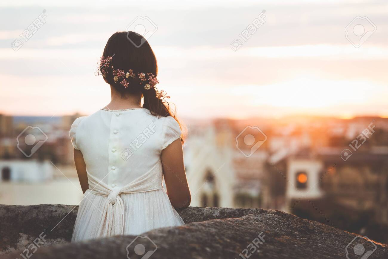 girl in communion dress looking at city on sunset - 131491707