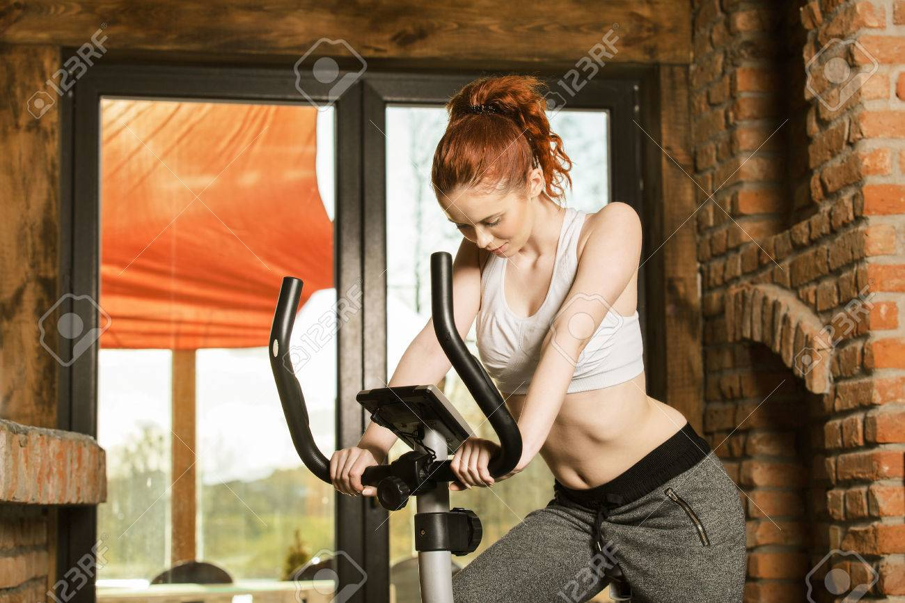 Active young woman doing exercise on bicycle at home  Fitness