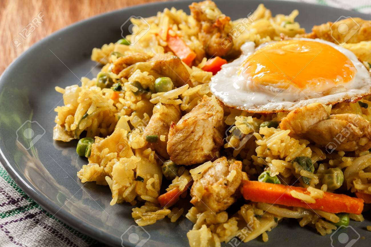 Fried rice nasi goreng with chicken egg and vegetables on a plate. Indonesian cuisine. - 130851452