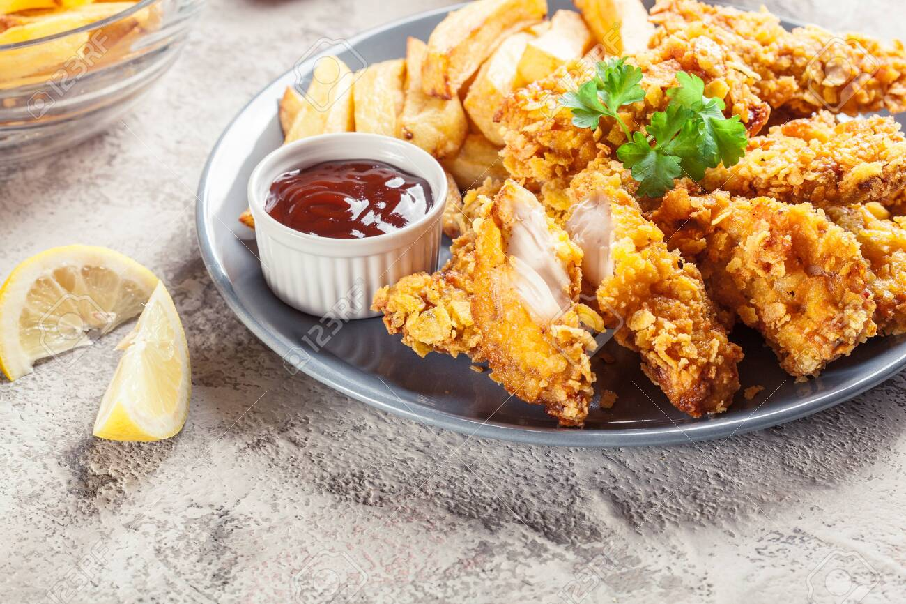 Chicken strips in cornflakes breadcrumb served with french fries - 144030053