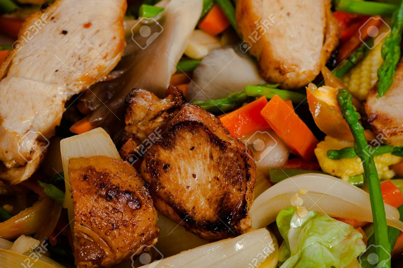 low fat asian vegetable dish with chicken in a wok on wooden table Stock  Photo -