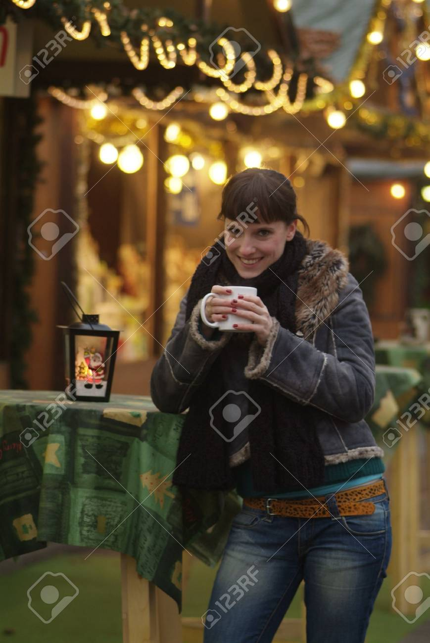 a dark haired woman drinks glogg at the market stall Stock Photo - 726985