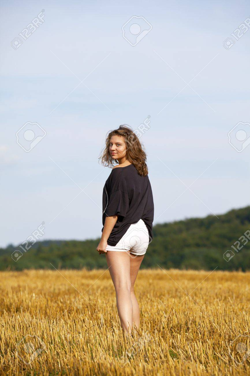 a beautiful blond smiling teenage girl looking back while walking away, photographed in the late evening sun on an acre Stock Photo - 7758537